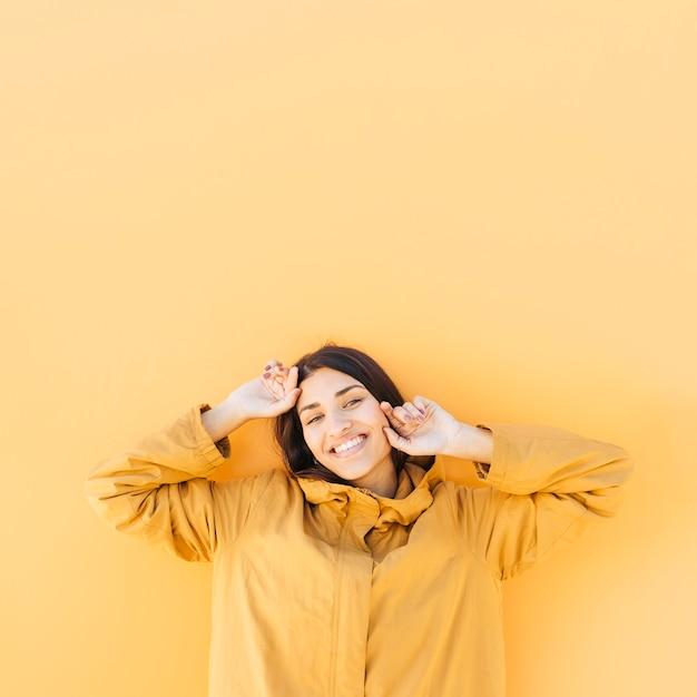 陽気な女性が普通の黄色を背景にポーズ 無料写真