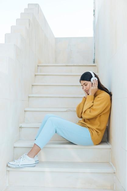 Женщина отдыхает, слушая музыку в наушниках, сидя на ступеньках Бесплатные Фотографии