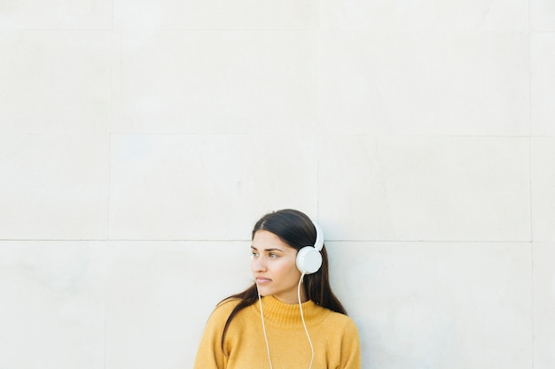 思いやりのある若い女性リスニング音楽立っている白い壁 無料写真