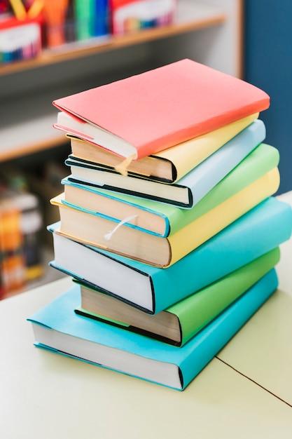 Стопка разноцветных книг на столе Бесплатные Фотографии