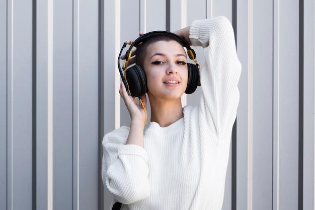 ヘッドフォンを身に着けている坊主頭と軽薄な若い女性 無料写真