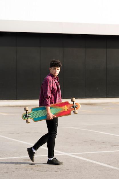 Черный подросток в клетчатой рубашке гуляет с лонгбордом Бесплатные Фотографии