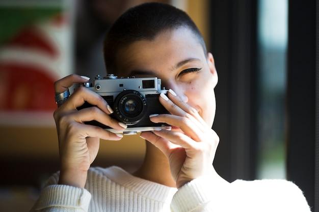 短い髪の女性がビンテージカメラで写真を撮る 無料写真