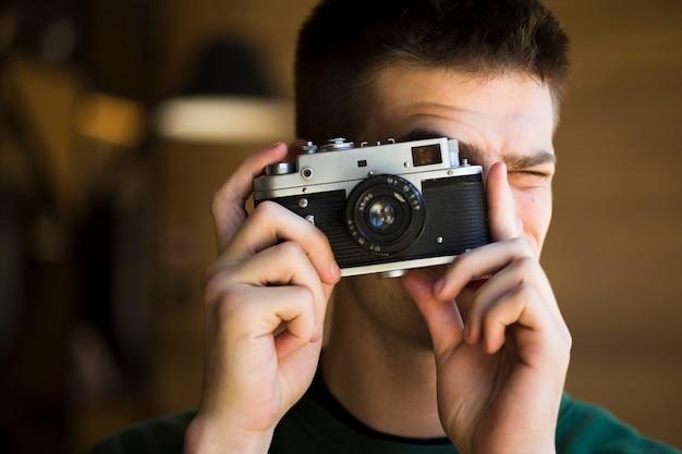 ビンテージカメラで写真を撮る若いマッド 無料写真