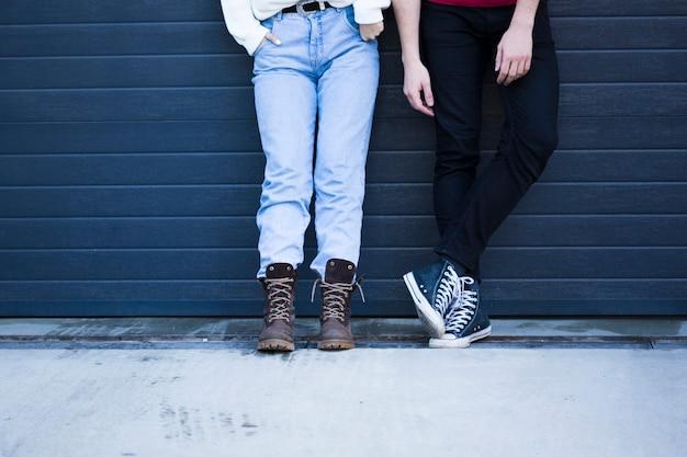 水色の壁に対して立っているカジュアルな服装のカップル 無料写真