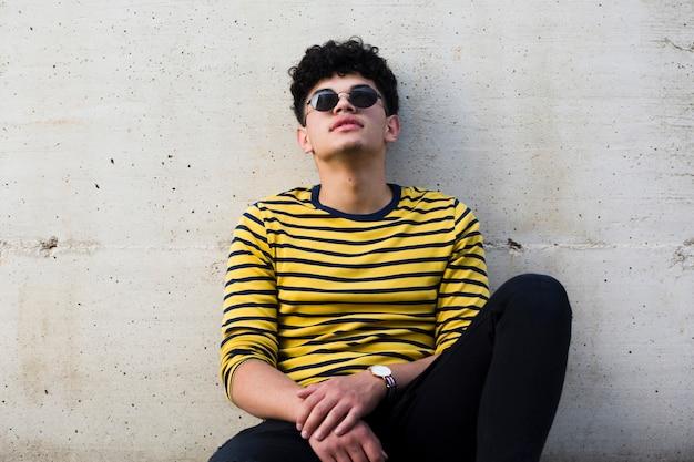 Молодой этнический кудрявый мужчина в темных очках, опираясь на серую бетонную стену Бесплатные Фотографии