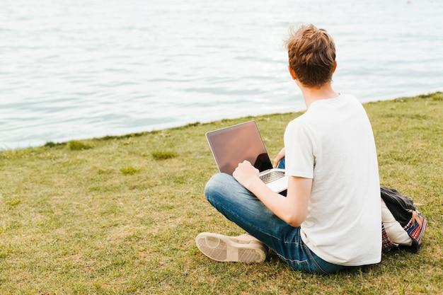 湖のほとりのラップトップに取り組んでいる男 無料写真