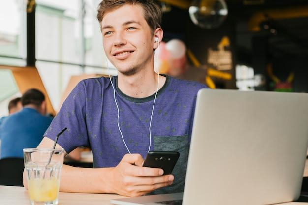 ノートパソコンとヘッドフォンと若い男 無料写真