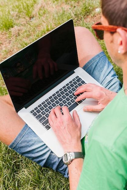 Цветочная мужчина работает на ноутбуке в парке Бесплатные Фотографии