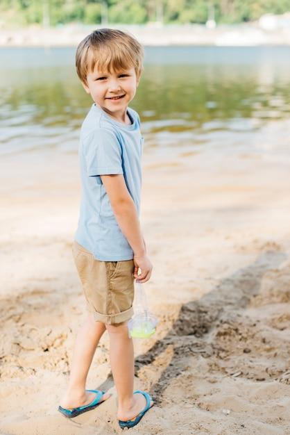 ゴーグルを運ぶ少年はビーチで好転します。 無料写真