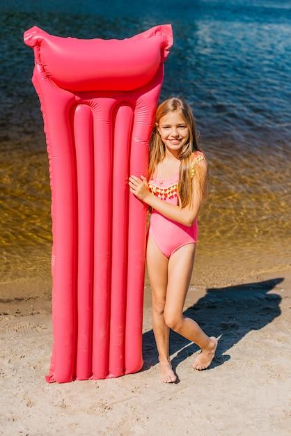 海岸に色の空気マットでかわいい女の子 無料写真