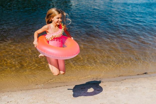 海辺でジャンプ水着でかなりのんきな女の子 無料写真