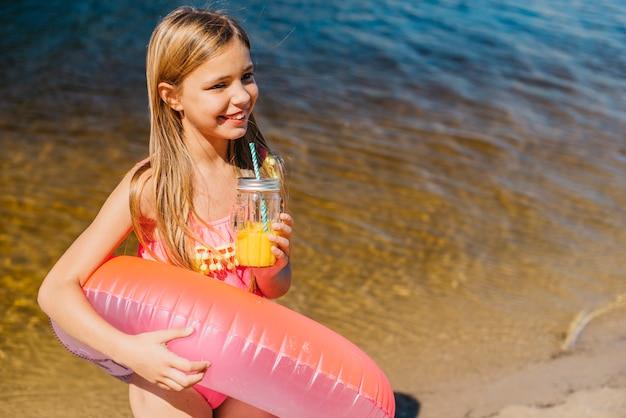 海岸に明るい水泳リングで興奮している女の子 無料写真