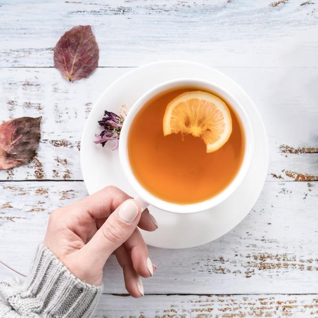 ぼろぼろの表面にお茶のカップを保持している作物女性 無料写真