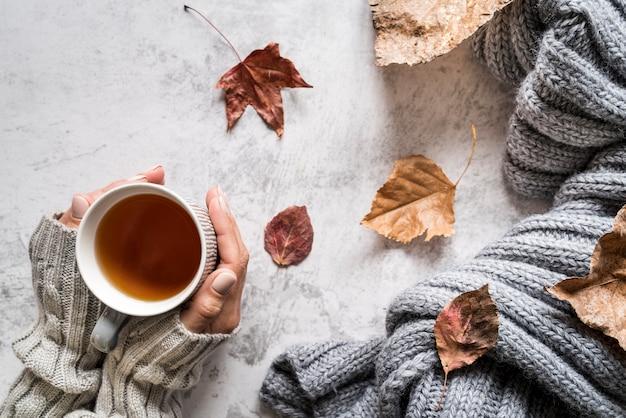熱いお茶のカップを持つ女性をトリミングします。 無料写真