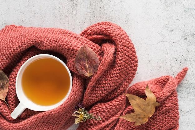 Чашка с напитком в трикотаж и листья Бесплатные Фотографии