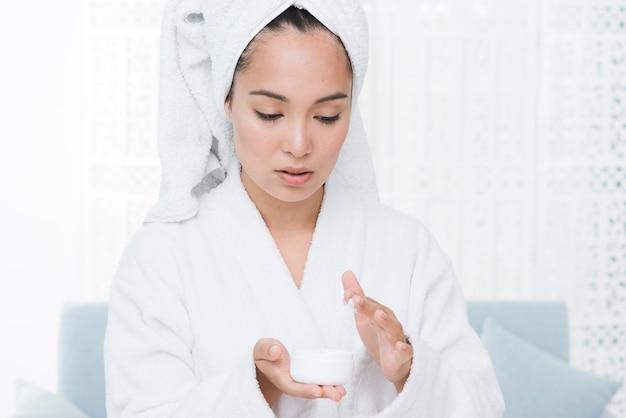 Женщина, используя косметический крем в спа Бесплатные Фотографии