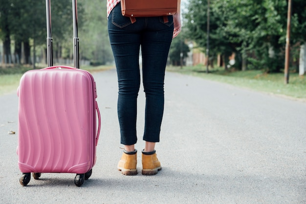 公園でピンクの荷物を持つ少女の背面図 無料写真