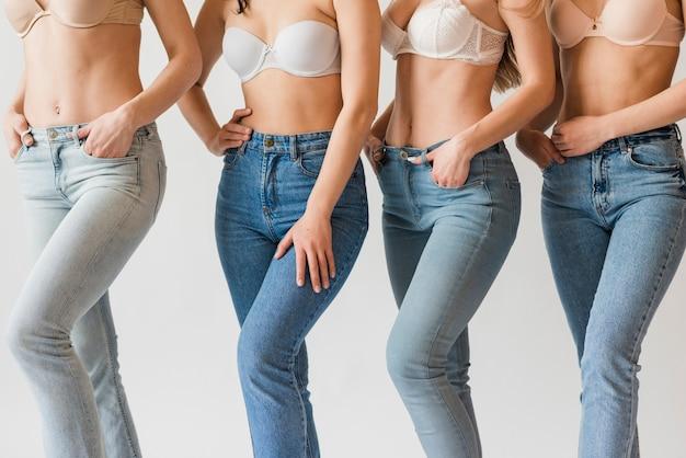 ブラジャーとジーンズでポーズをとって多様な女性のグループ 無料写真