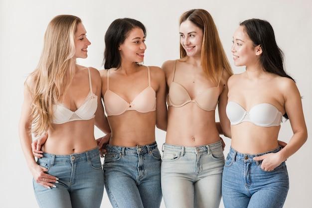 Многорасовая группа молодых женщин в бюстгальтерах, обнимающихся и улыбающихся Бесплатные Фотографии