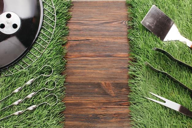 木製の背景上の草のマットの上の様々なバーベキュー用具のセット 無料写真