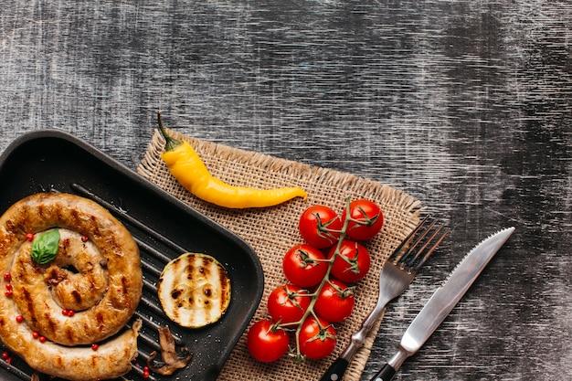 カタツムリのソーセージを織り目加工の背景に鍋に赤胡椒とバジルの葉を飾る 無料写真