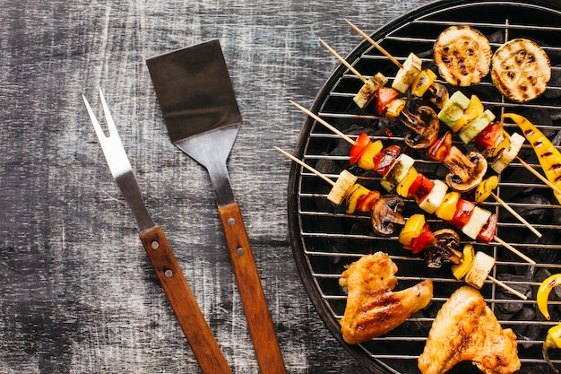 木製の背景上のバーベキューグリルで焼き肉の準備 無料写真