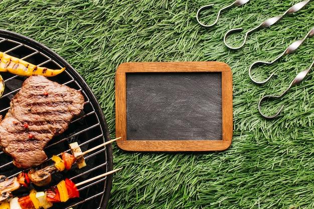 白紙のスレートと芝生の上の金属串の近くのバーベキューグリルで焼くステーキとソーセージ 無料写真