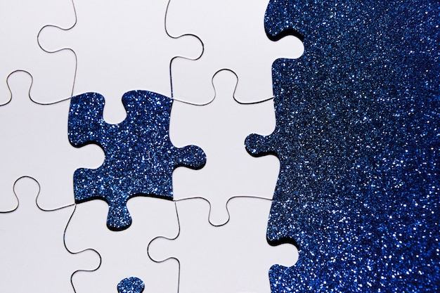 青いキラキラ背景にパズルのピースのオーバーヘッドビュー 無料写真