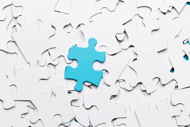 白いパズルのピースの上の青いジグソーパズルのピース 無料写真