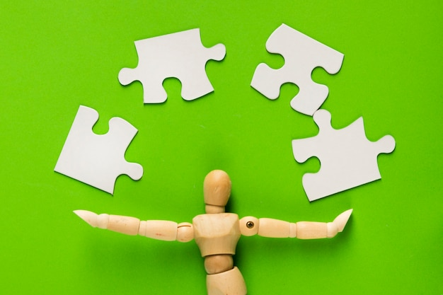 緑の背景の上の木製の人物像のパズルのピース 無料写真
