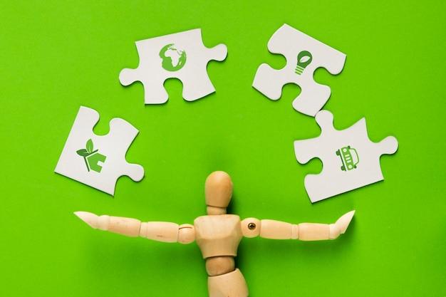 緑の上の人間の指で白いパズルのピースのエコロジーアイコン 無料写真