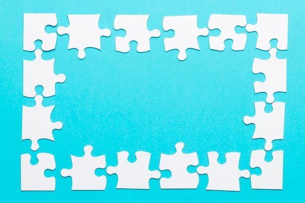 青い背景にジグソーパズルフレームの高角度のビュー 無料写真