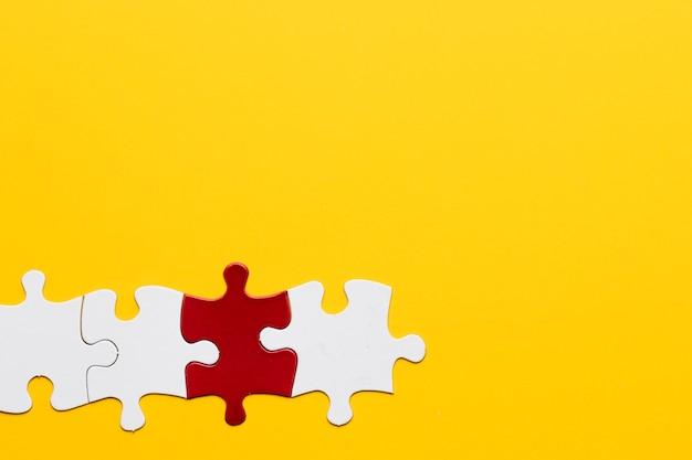 黄色のコピースペースの背景を持つ赤と白のパズルのピース 無料写真
