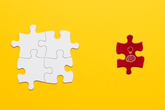 黄色の背景上の白い共同パズルのピースの近くに立っている赤いパズルのピース上のアイデアアイコン 無料写真