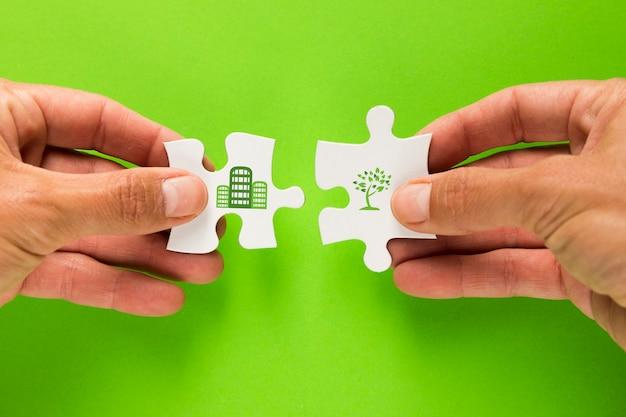 男性の手が緑色の表面上のエコロジーアイコンと白いパズルに参加 無料写真