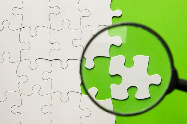 緑の背景に白のジグソーパズルの上の虫眼鏡 無料写真