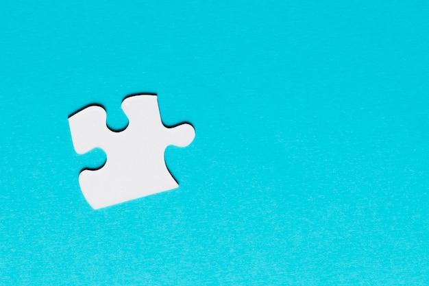 青い背景に白いシングルパズルのピース 無料写真