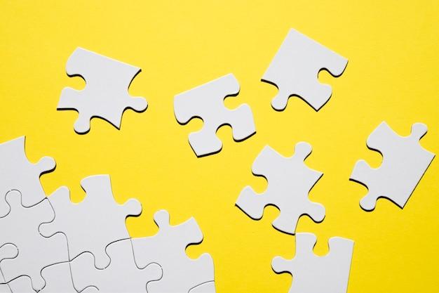 黄色の背景に別々の白いパズルのピース 無料写真