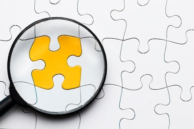 白いパズルと接続されている黄色のパズルのピースの上の虫眼鏡のクローズアップ 無料写真
