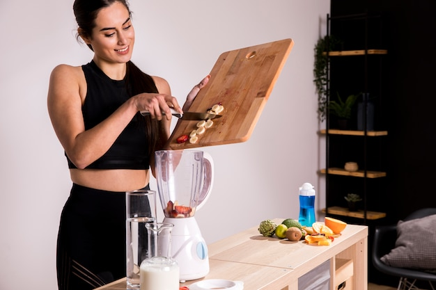 デトックスジュースを準備するフィットネス女性 無料写真