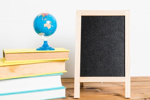 木製のテーブルに空の黒板と本の小さなグローブ 無料写真