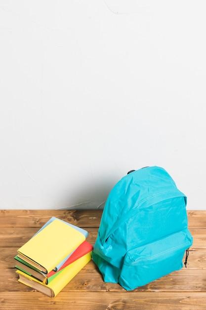 木製テーブルの上の空白のカバーと本と青いカバン 無料写真