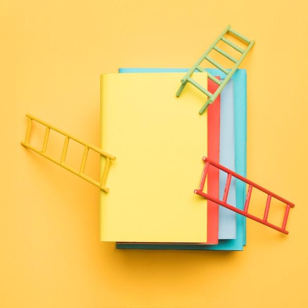 黄色の背景にカラフルな空白の本のスタック上の明るいはしご 無料写真