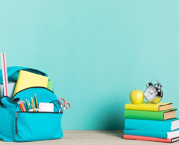 書籍の目覚まし時計と供給の学校のバックパックのスタック 無料写真