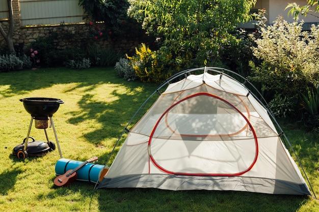 バーベキューグリルとウクレレの芝生の上でキャンプのテント 無料写真