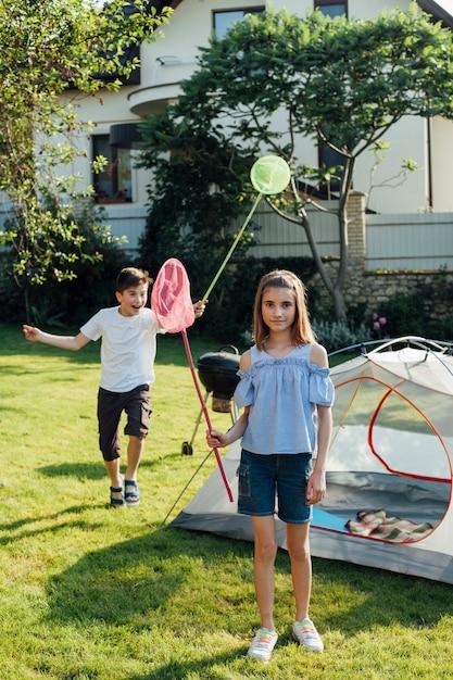 Брат и сестра ловят бабочек и жуков сеткой для бабочек в парке Бесплатные Фотографии