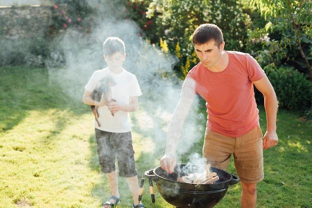 Мальчик держит собаку стоя возле своего отца, приготовление пищи в парке Бесплатные Фотографии