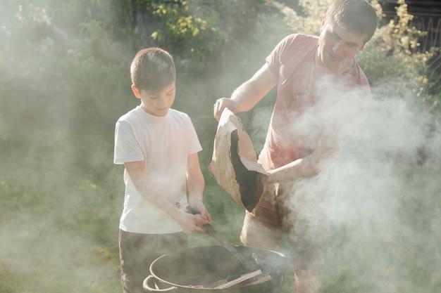 父と息子が食べ物を準備するためにバーベキューに石炭を入れて 無料写真