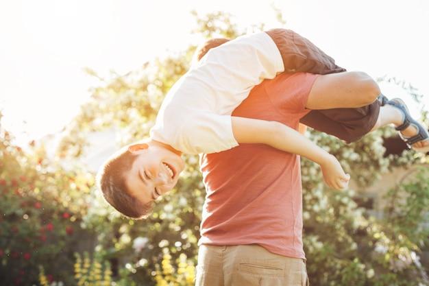 Улыбающийся сын и отец с удовольствием в парке Бесплатные Фотографии